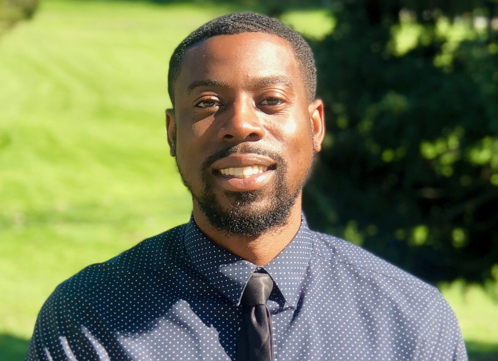 Dr. Lamar Johnson wearing a navy button up with gray dots and a black tie.
